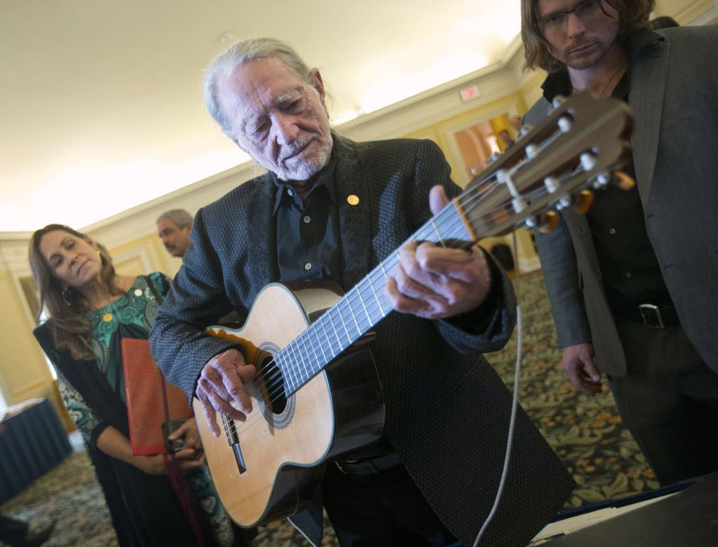 Musician Willie Nelson plays a guitar that was donated to the Library of Congress by Burl Ives, during a tour of items from Musical Division at the Library of Congress in Washington, Tuesday, Nov. 17, 2015.