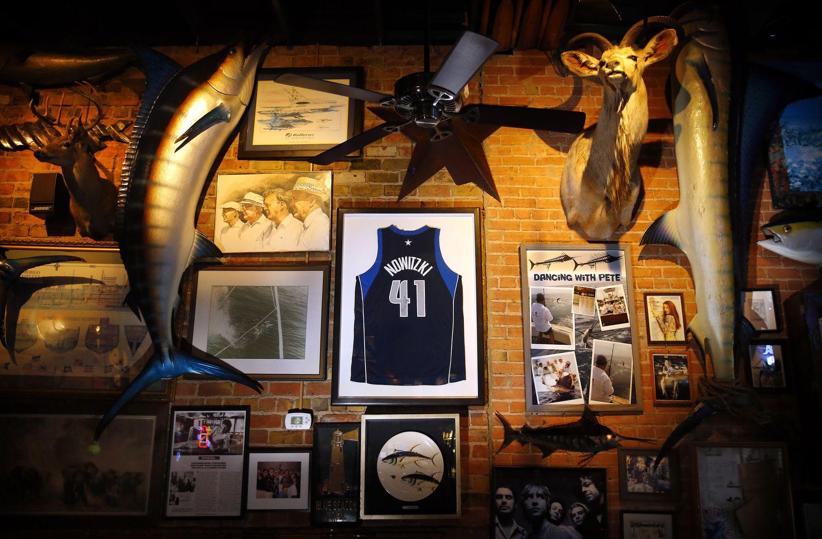 A jersey of Dallas Mavericks Dirk Nowitzki hangs between a pair of mounted swordfish at St. Pete's Dancing Marlin in Deep Ellum in Dallas.