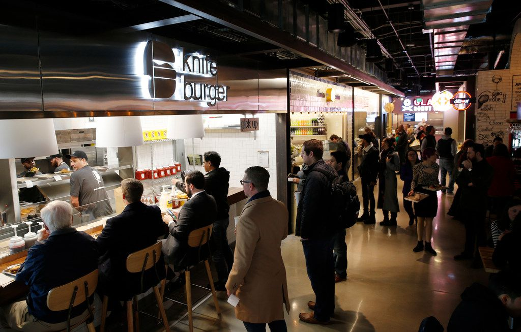 People wait in line at knife burger as others make their way around Legacy Hall during the lunch hour at Legacy Hall in Plano, on Thursday, December 7, 2017. Legacy Hall has over 30 food and drink stalls for customers to choose from.