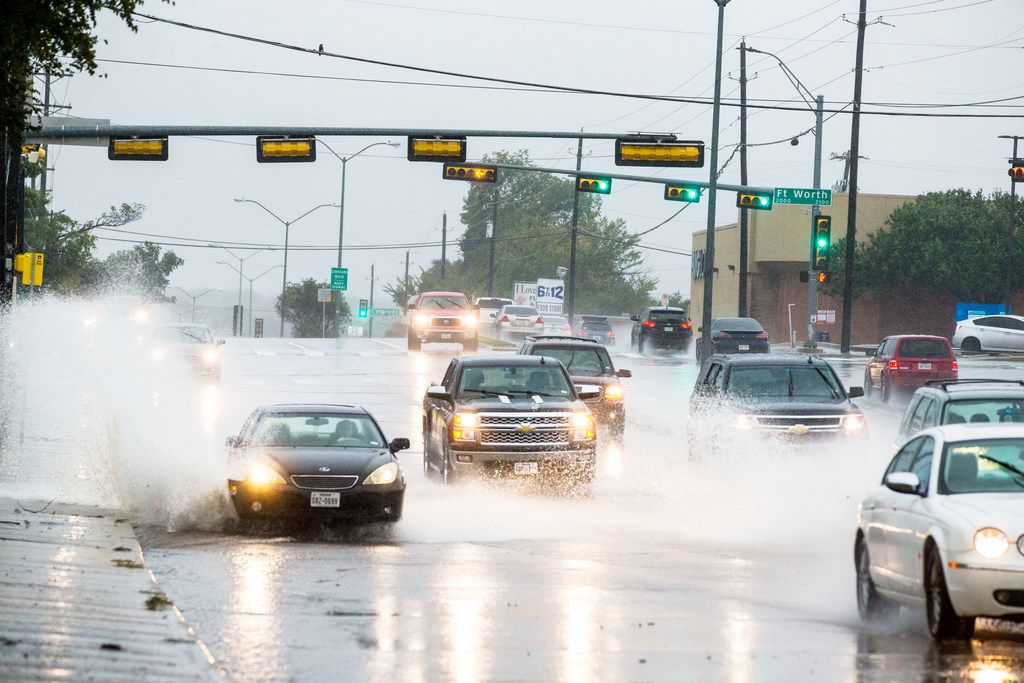 Cars drive through standing water at North Hampton Road in Dallas on Oct. 13, 2018.