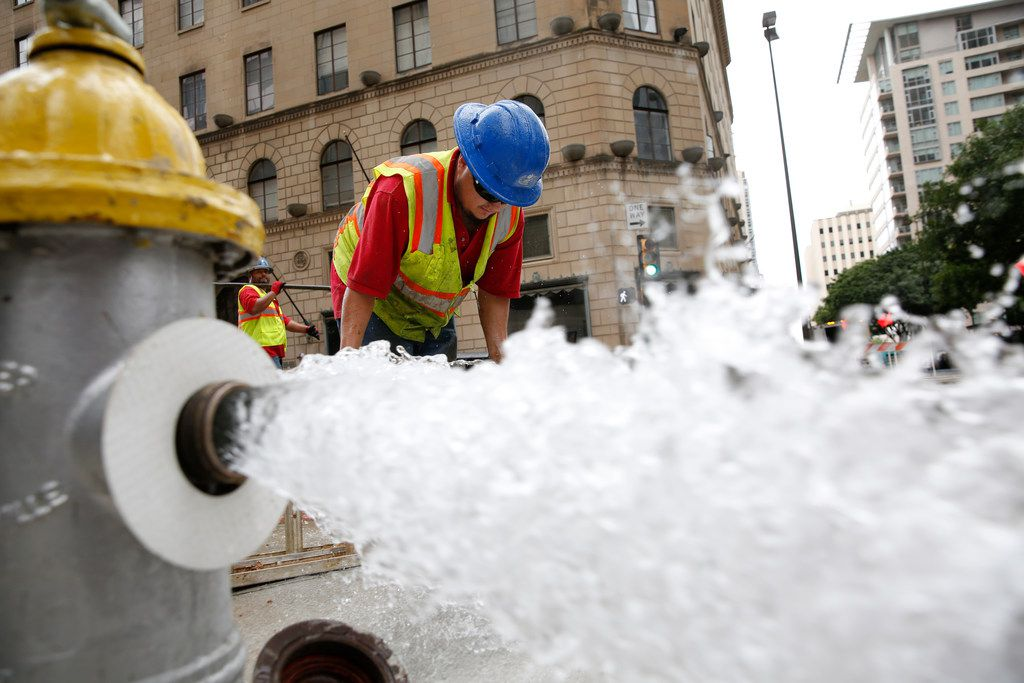 Luis Ortiz cleans off a muddy step ladder after fixing a water main break at St. Paul and Elm streets in downtown Dallas on Friday, Aug. 10. The broken waterline sent water gushing through downtown Dallas, closed roads and shut down water service in the area.