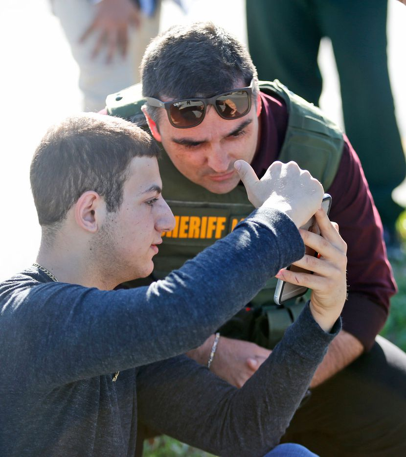 A student shows a law enforcement officer a photo or video from his phone, Wednesday, Feb. 14, 2018, in Parkland, Fla. A shooting at Marjory Stoneman Douglas High School sent students rushing into the streets as SWAT team members swarmed in and locked down the building. Police were warning that the shooter was still at large even as ambulances converged on the scene and emergency workers appeared to be treating those possibly wounded. (AP Photo/Wilfredo Lee)