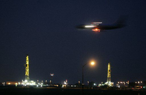 Incoming American Airlines jet with natural gas wells in the background at dusk at DFW airport. Photographed Aug. 17, 2008.