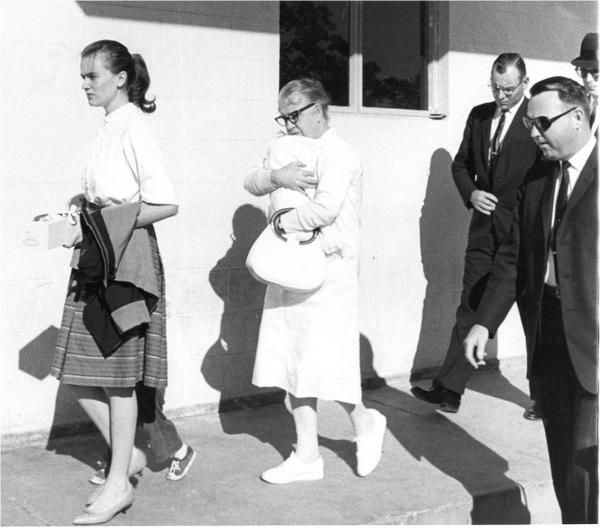 Secret Service agents, including Howard, follow Marina Oswald (left), holding June's hand, and Marguerite holding Rachel, into Parkland Memorial Hospital to see Lee Harvey Oswald.