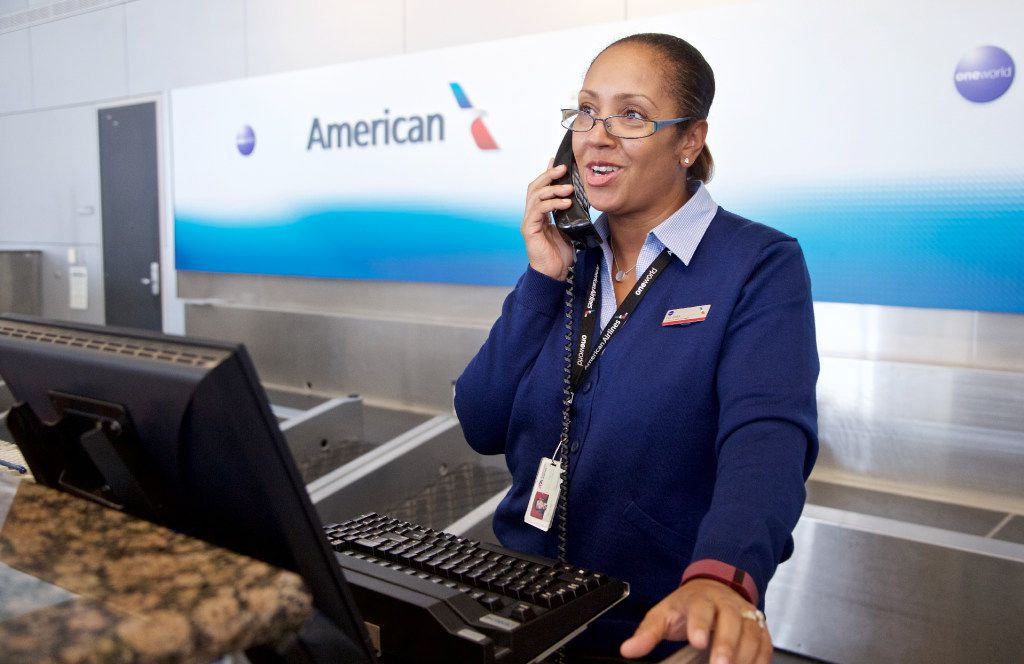 American Airlines Customer Service Agent Yolanda Walter, wearing one of the airline's new uniforms, helps customers at DFW Airport, Tuesday, September 20, 2016. (Brandon Wade/Special Contributor)