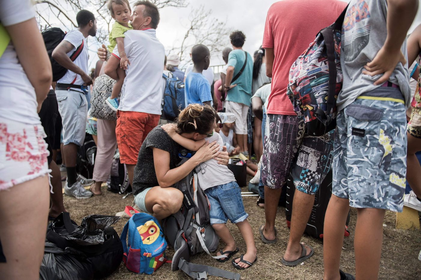 A mother comforts her child as they wait in front of Grand-Case Esperance airport entrance to leave Saint-Martin, on September 10, 2017 on the French Carribean island of Saint-Martin after it was devastated by Irma hurricane. People on the islands of Saint Martin and Saint Barts turn to the colossal task of rebuilding after Hurricane Irma laid waste to their infrastructure and shattered their lives.