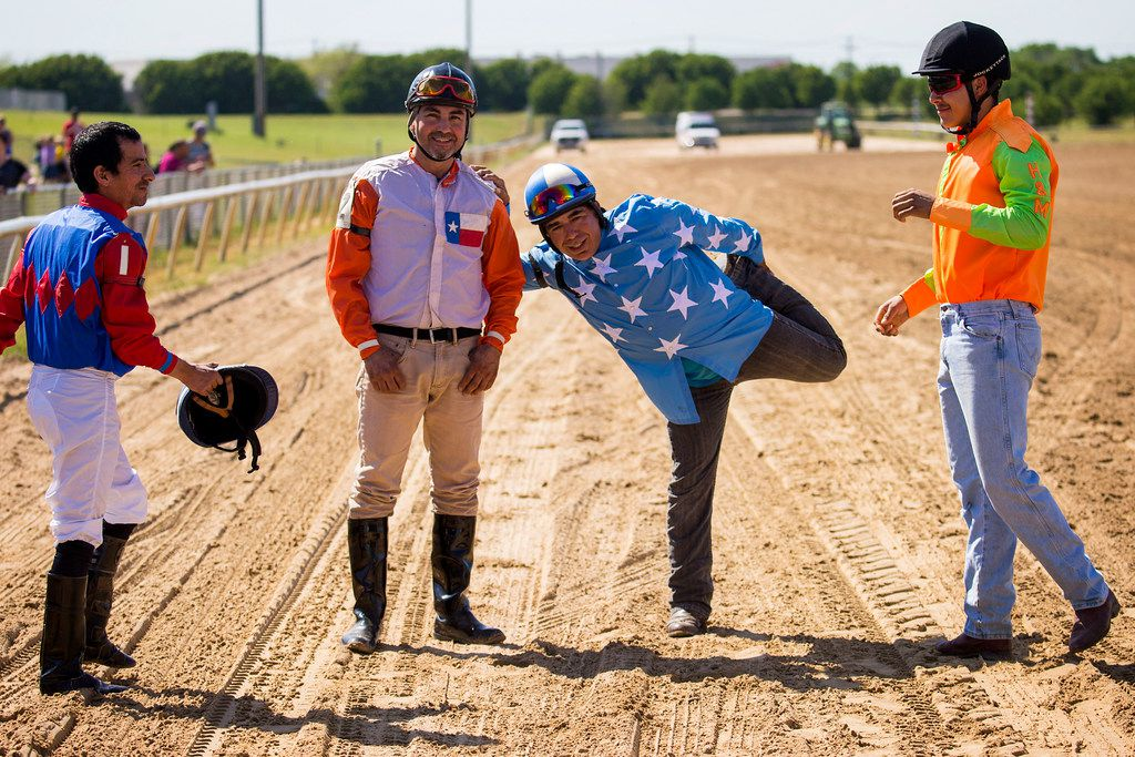 """From left, jockeys Daniel Benavides, Corey Alvarado, Alex Alvarado and Fernando Guerra stretch before mounting on zebras for a race during """"Extreme Racing"""" at Lone Star Park on Saturday, April 28, 2018, in Grand Prairie, Texas. Ridden by Lone Star Park jockeys, camels, ostriches and zebras took to the track between horse races, with each animal paired with a local non-profit charity. (Smiley N. Pool/The Dallas Morning News)"""