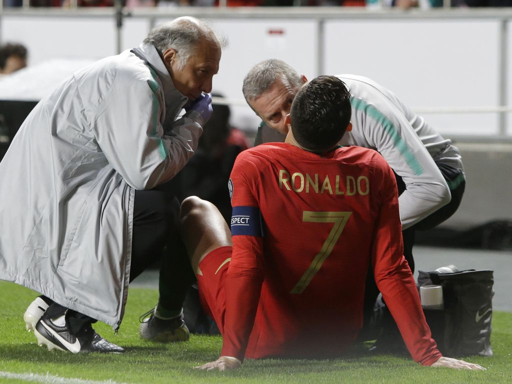 Cristiano Ronaldo recibe tratamiento médico tras sufrir una lesión en el juego de Portugal con Serbia. (AP Photo/Armando Franca)