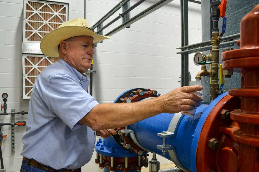 Public Works director Doug Hutcheson fills a cup with water at the water treatment plant in Wolfforth, Texas.