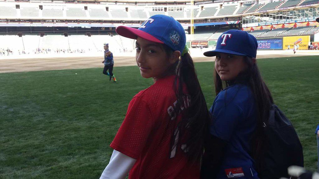 Tatyana Beltran (left) and Alicia Gonzales (right) take in Rangers Fan fest four years ago. The two girls will play in an inaugural girls baseball invitational called MLB Grit at Globe Life Park in Arlington this weekend. (Courtesy: Sandy Ramos)