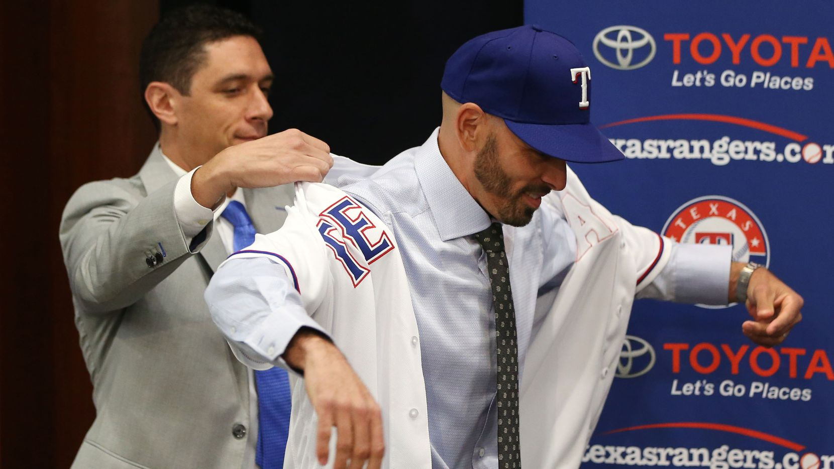 Texas Rangers' new manager Chris Woodward puts on his jersey with help from General Manager Jon Daniels (left) during a press conference announcing his position at Globe Life Park in Arlington, Texas on Monday, Nov. 5, 2018. (Rose Baca/The Dallas Morning News)