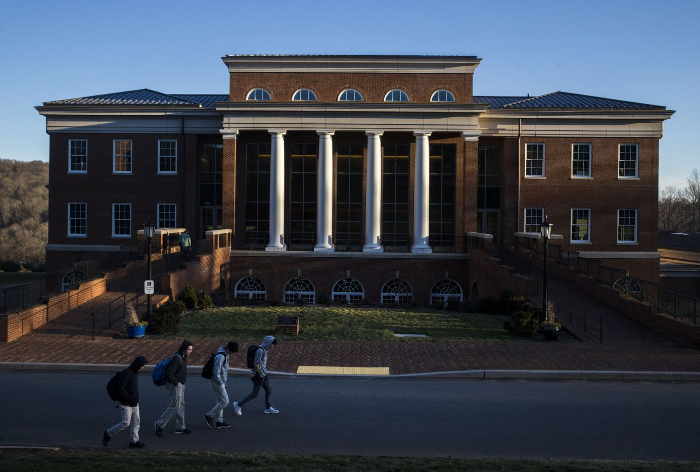 Students walk past Kenan Hall as sun descends at Woodberry Forest School in Orange, Va.