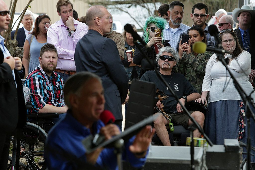 Shooting survivors Kris Workman (left) and Gunny Macias, with his wife Jennifer Macias (right), watch Gov. Greg Abbott speak during Remembering Sutherland Springs: One Year Later at First Baptist Church of Sutherland Springs on Sunday.