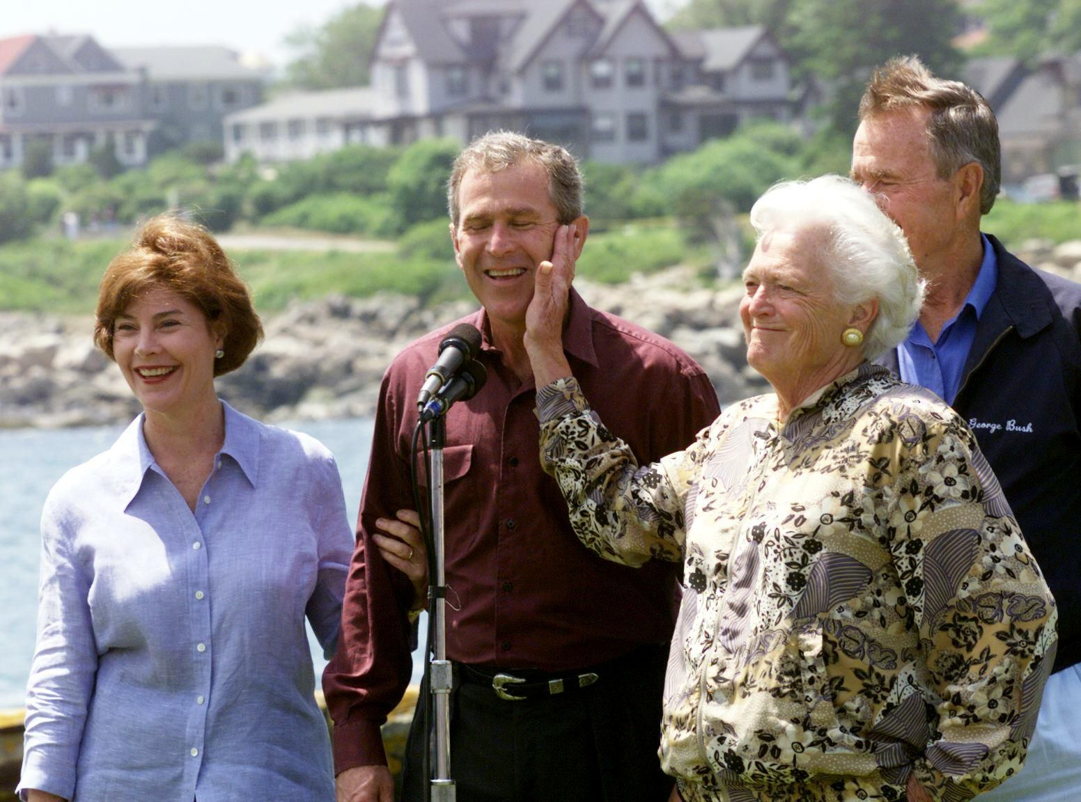 Barbara Bush playfully slaps her son George during a photo op at the family home in Kennebunkport, Maine, in June 1999. George W. Bush, standing with his wife, Laura, was Texas governor at the time.