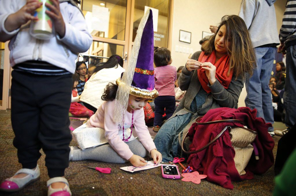 Families create paper masks during the Noon Year's Eve Party for youngsters at the Haggard Library in Plano in 2015.