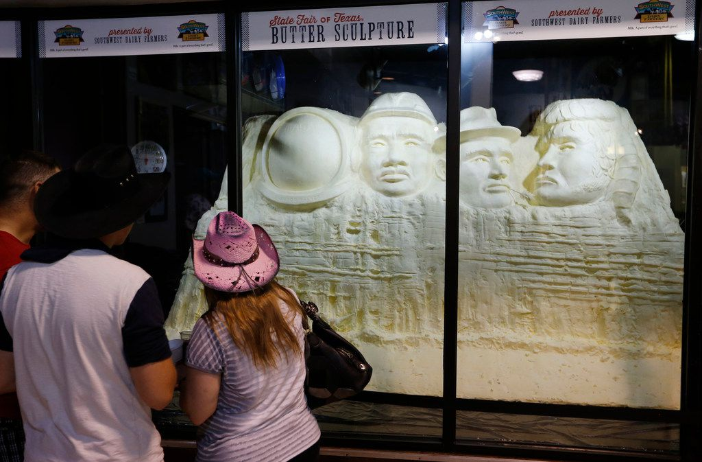 """People look at the """"Mount Muchmore"""" butter sculpture at the State Fair of Texas in Dallas on Sunday."""