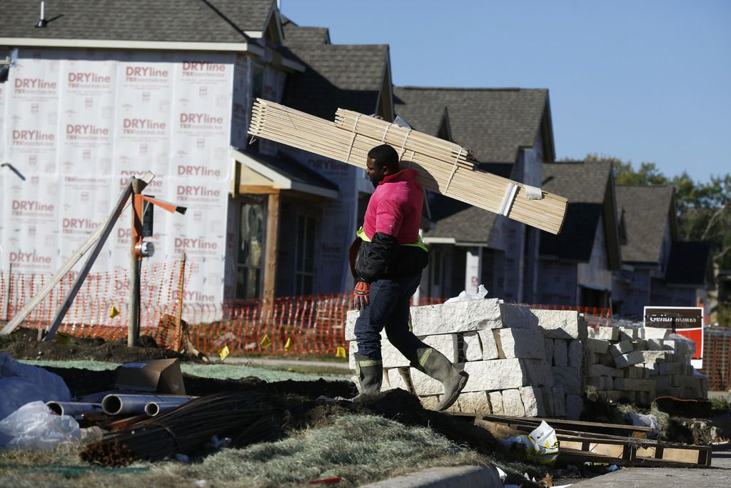 Friday James takes materials into a house under construction by Gehan Homes in 1600 block of Booker Lane in Sabine Park Estates in Plano, Texas on Nov. 16, 2018.