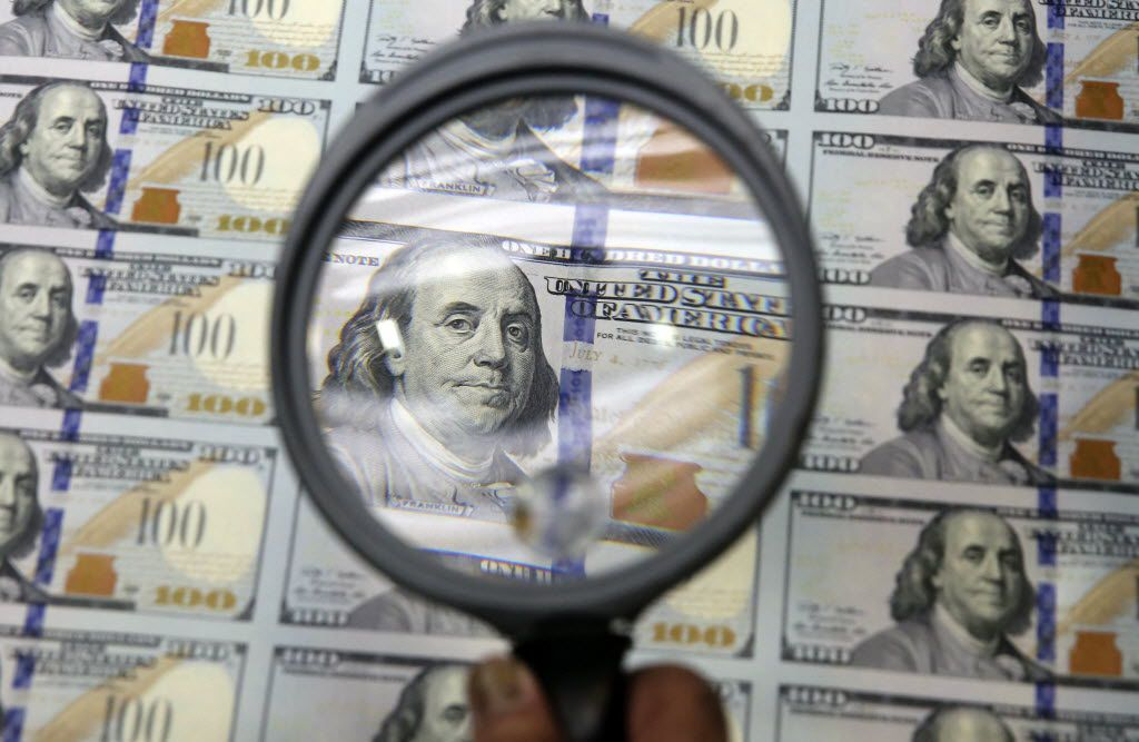 In this Sept. 24, 2014 file photo, a sheet of uncut $100 bills is inspected during the printing process at the Bureau of Engraving and Printing Western Currency Facility in Fort Worth, Texas.  (AP Photo/LM Otero, File)