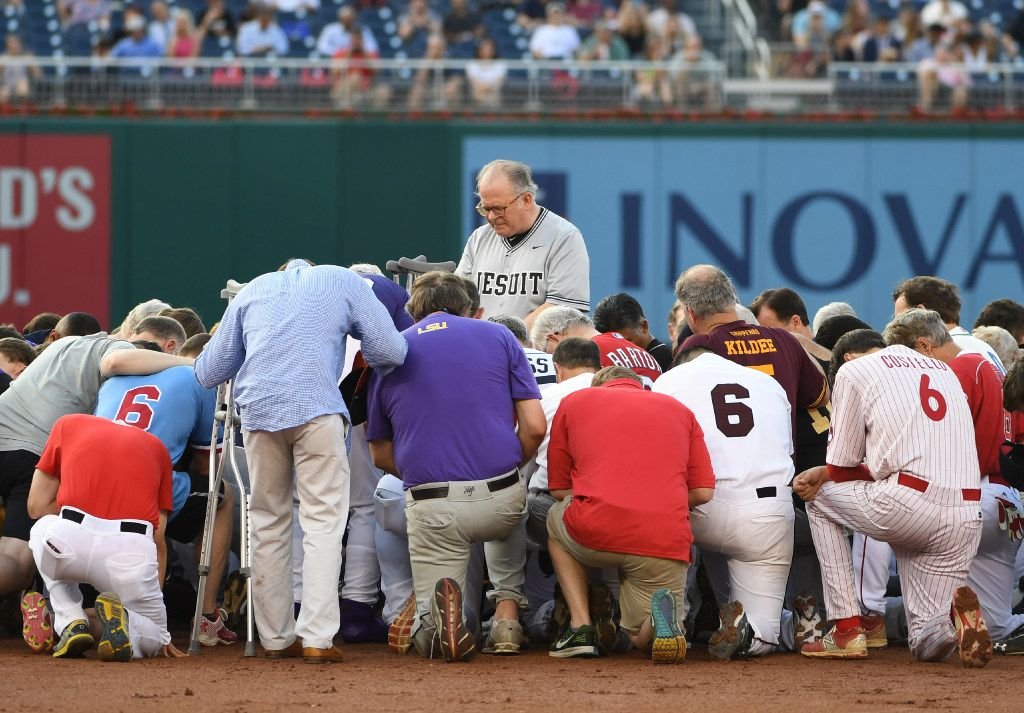 Camaraderie as thick as the humidity: The House chaplain led Democrats and Republicans in prayer at second base before the Congressional Baseball Game on Thursday evening at Nationals Park in Washington, D.C.