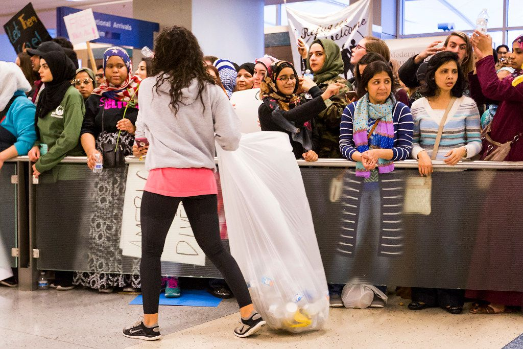 Protestors gather trash at DFW International Airport where they gathered in opposition to President Donald Trump's executive order barring certain travelers on Sunday, Jan. 29, 2017.  (Smiley N. Pool/The Dallas Morning News)