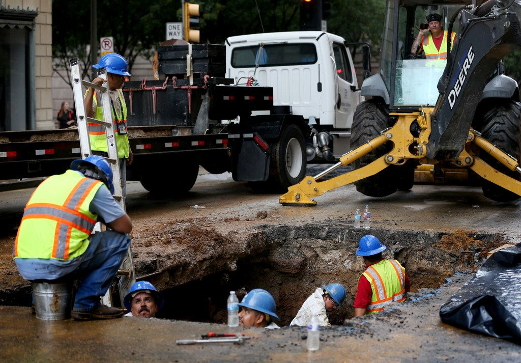 Crews work to fix a water main break at St. Paul and Elm streets in downtown Dallas on Friday, Aug. 10. The broken waterline sent water gushing through downtown Dallas, closed roads and shut down water service in the area.