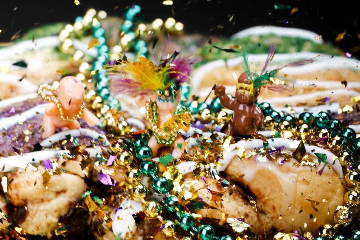 Decorated Mardi Gras babies stand atop a king cake with beads and confetti.