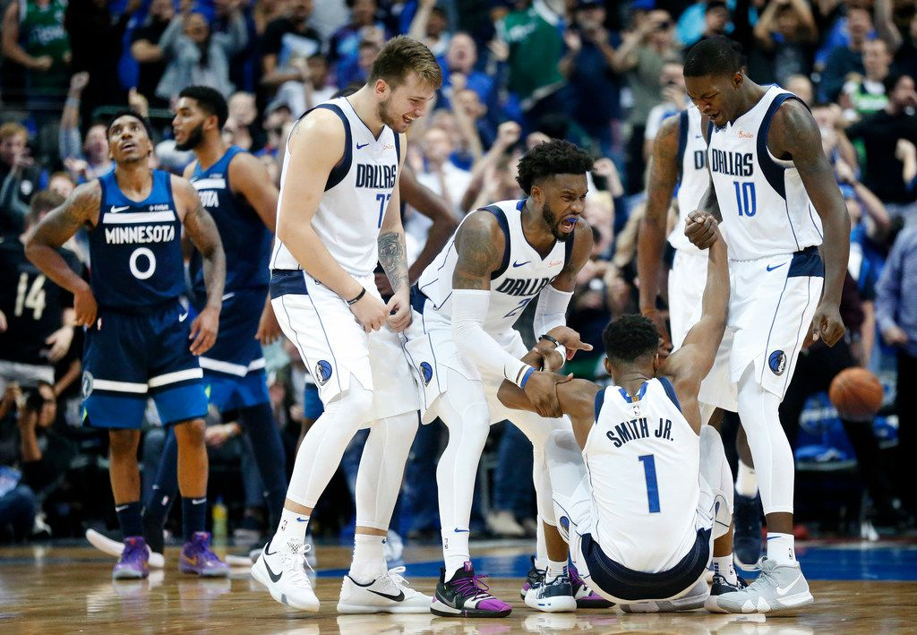 Dallas Mavericks guard Luka Doncic (77), guard Wesley Matthews (23) and forward Dorian Finney-Smith (10) congratulate guard Dennis Smith Jr. (1) for hitting a late fourth quarter shot after being fouled by the Minnesota Timberwolves  at the American Airlines Center in Dallas, Saturday, October 20, 2018. (Tom Fox/The Dallas Morning News)