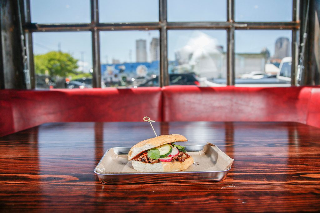 """""""The Phat Banh Mi,"""" soy marinated shaved pork, pickled carrots, radish, cucumber, Serrano, Cilantro, topped with Maggie sauce at Off The Cuff in Deep Ellum, Thursday, April 18, 2019. (Brandon Wade/Special Contributor)"""