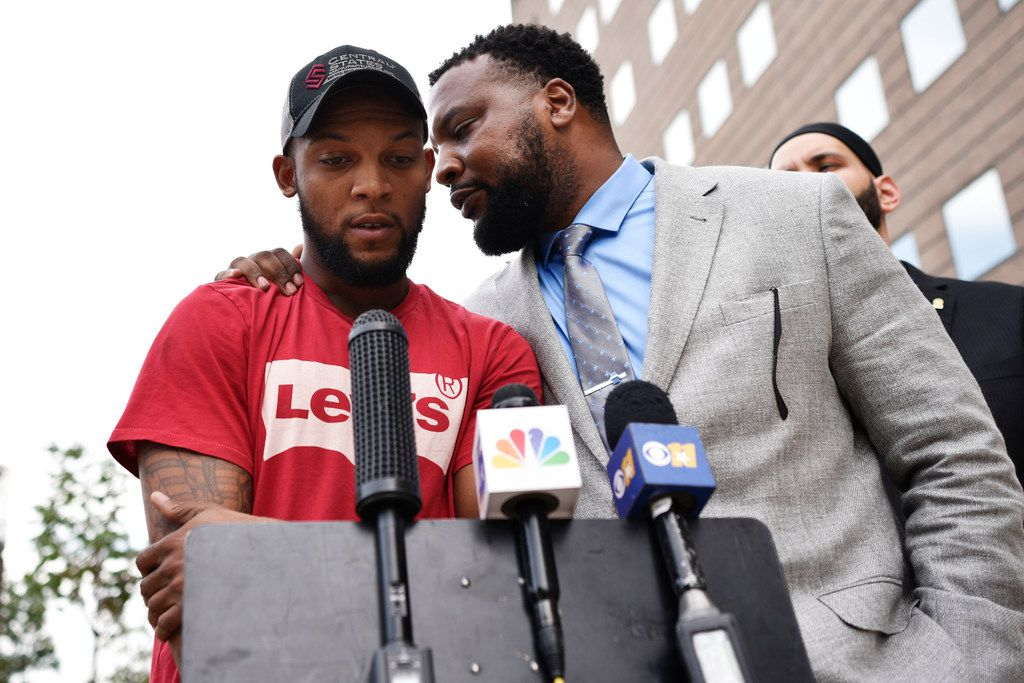 Attorney Lee Merritt whispers to Lyndo Jones during a news conference outside the Frank Crowley Courts Building in Dallas. Jones was shot by a Mesquite police officer who was ultimately acquitted of aggravated assault.