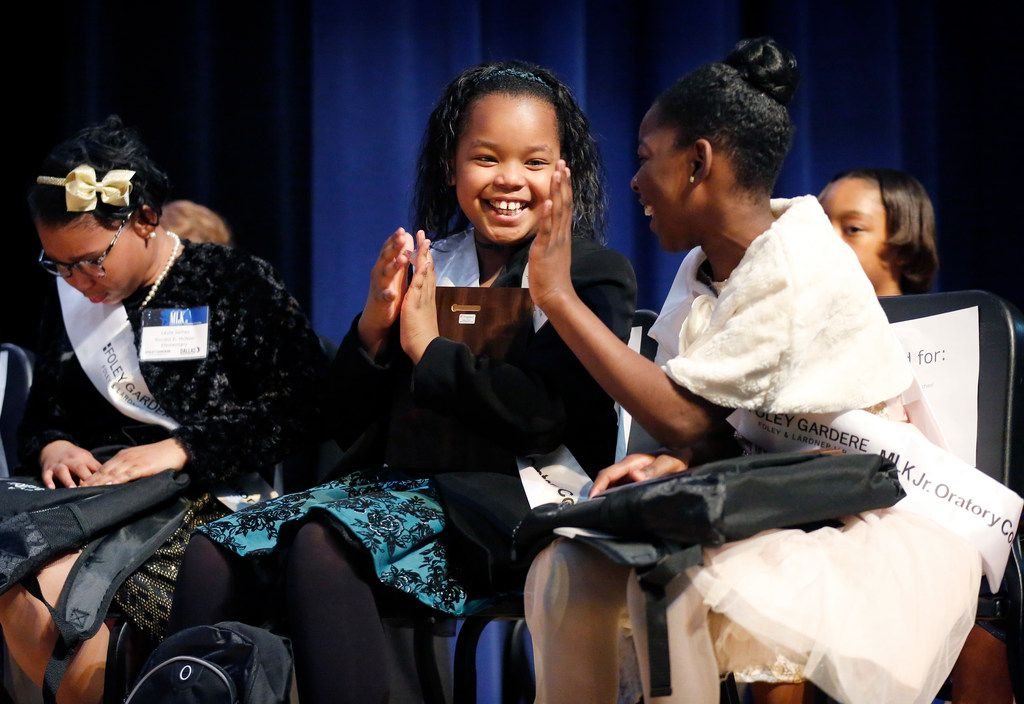 First-place winner Jasira King (center) is congratulated by the third-place winner, Tynia Matts, a fifth-grader at John Neely Bryan Elementary, after the winners of the 27th annual Foley Gardere MLK Jr. Oratory Competition were announced.