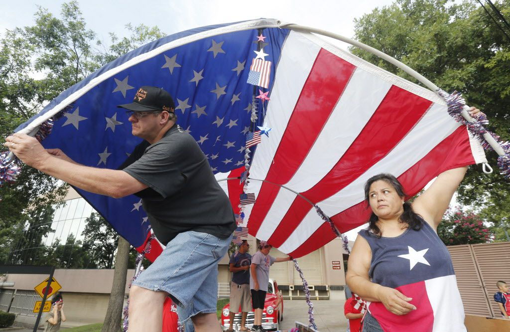 Fred Webb, left, and Selena Hernandez, work on a float for the Irving Boys Football Association, prior to the Irving 4th of July parade in Irving, Texas on Saturday, July 4, 2015.