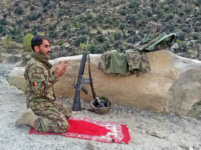 An Afghan army soldier prayed while fighting Taliban insurgents last week in the rugged Dangam district.