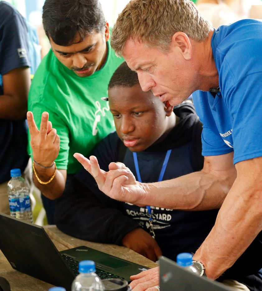 Hall of Fame Dallas Cowboys quarterback and United Way of Metropolitan Dallas annual campaign chairman Troy Aikman (right) flashes two fingers to a laptop camera during a machine learning example with Oliver Holmes Humanities and Communications Academy eighth grader Terrance Williams and Mr. Cooper Chief Technology Officer Sridhar Sharma (left) during a STEM related project, Friday, April 13, 2018 in Dallas. Aikman joined 150 corporate volunteers from Mr. Cooper, Texas Instruments and TXU Energy in leading more than 300 students in STEM-related interactive projects. (Tom Fox/The Dallas Morning News)
