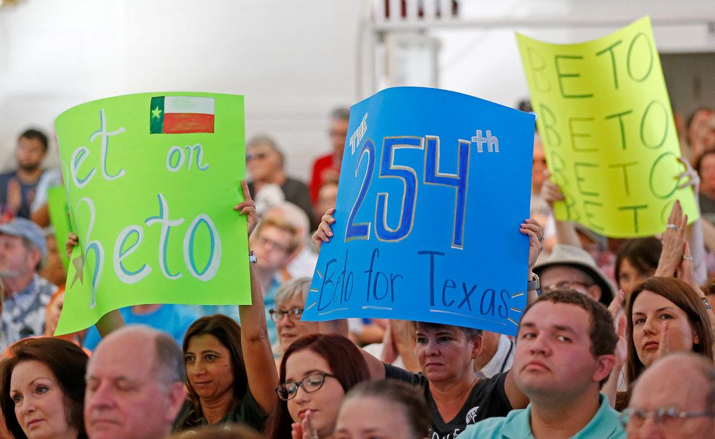Supporters hold up signs while Congressman Beto O'Rourke speaks during a town hall at the Historic Santa Fe Train Depot in Gainesville.