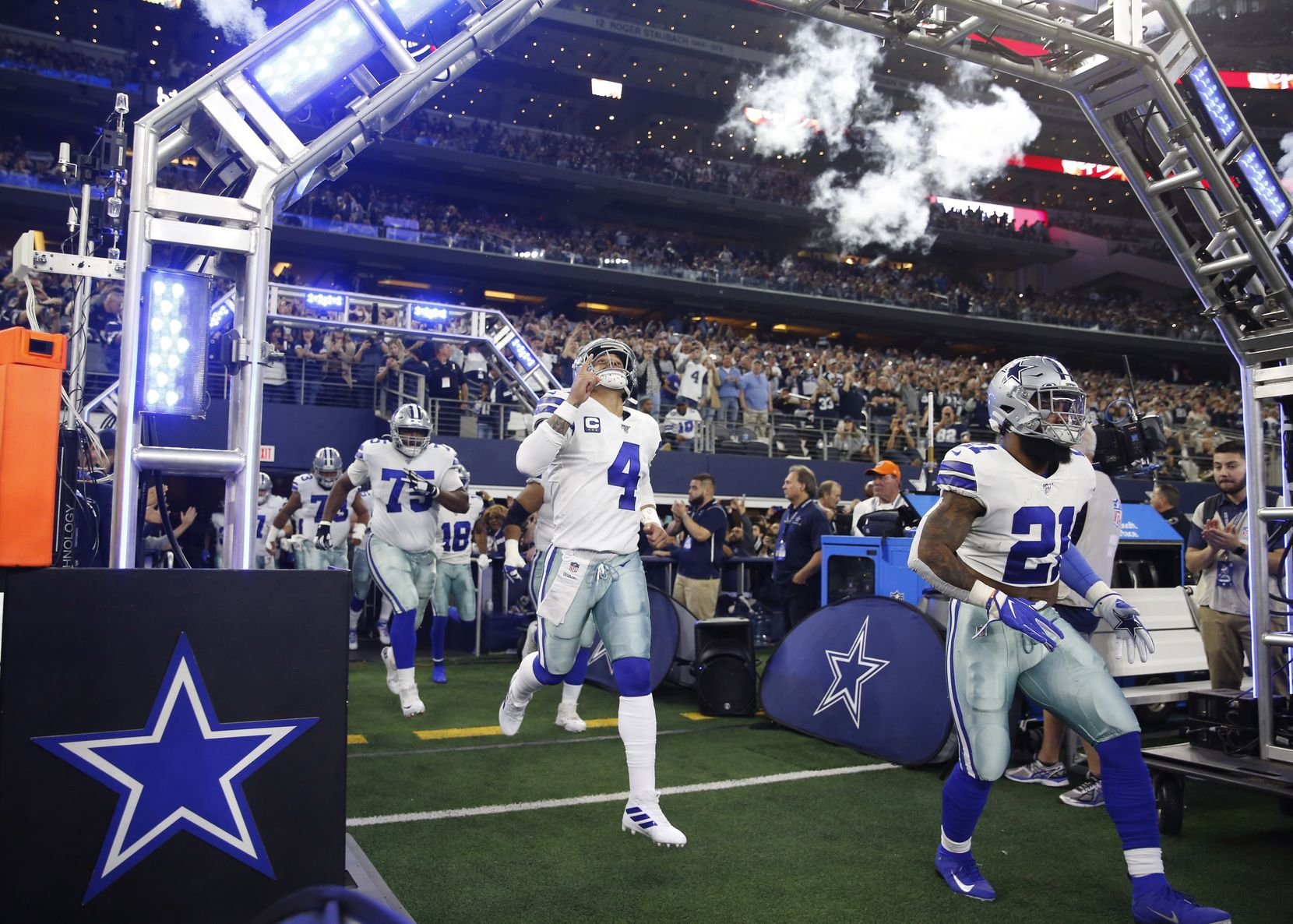 Dallas Cowboys quarterback Dak Prescott (4), Dallas Cowboys running back Ezekiel Elliott (21) and players take the field as they are introduced before playing against the Buffalo Bills at AT&T Stadium in Arlington, Texas on Thursday, November 28, 2019. (Vernon Bryant/The Dallas Morning News)
