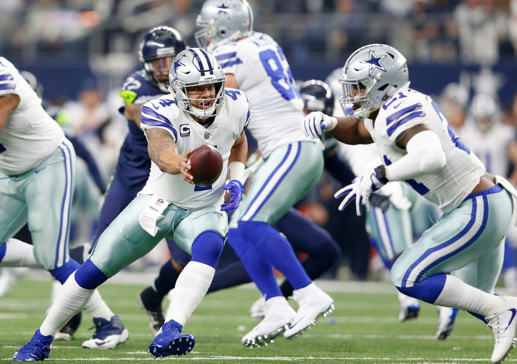 Dallas Cowboys quarterback Dak Prescott (4) hands the ball off to Dallas Cowboys running back Ezekiel Elliott (21) in a game against the Seattle Seahawks during the first half of play at AT&T Stadium in Arlington, Texas on Sunday, December 24, 2017. (Vernon Bryant/The Dallas Morning News)