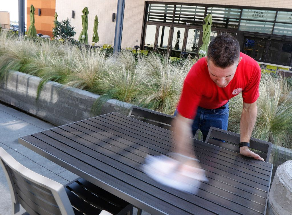 Corey Ahrens, 37, wipes off outdoor tables at Fish City Grill in Richardson, Texas, on Tuesday. He starts his day with a 45-minute commute, including two long walks and a five-minute train ride on DART. He works as key manager, server and bartender about 50 hour a week.
