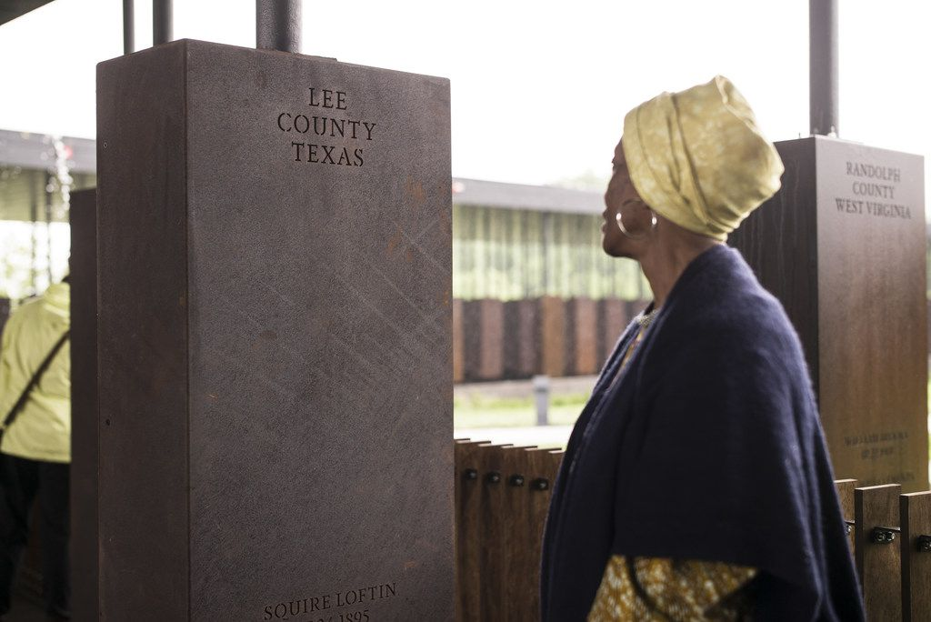 """Wretha Hudson, 73, discovers a marker commemorating lynchings in Lee County, Texas while visiting the National Memorial For Peace And Justice on April 26, 2018 in Montgomery, Alabama. Hudson, whose father's family came to Alabama from Lee County decades earlier, said the experience was overwhelming. """"It's a combination of pride and strength, for my people. In our culture, rain is a sign of acceptance from our ancestors. So the rain is a sign of their acceptance for this day."""" The memorial is dedicated to the legacy of enslaved black people and those terrorized by lynching and Jim Crow segregation in America. Conceived by the Equal Justice Initiative, the physical environment is intended to foster reflection on America's history of racial inequality."""