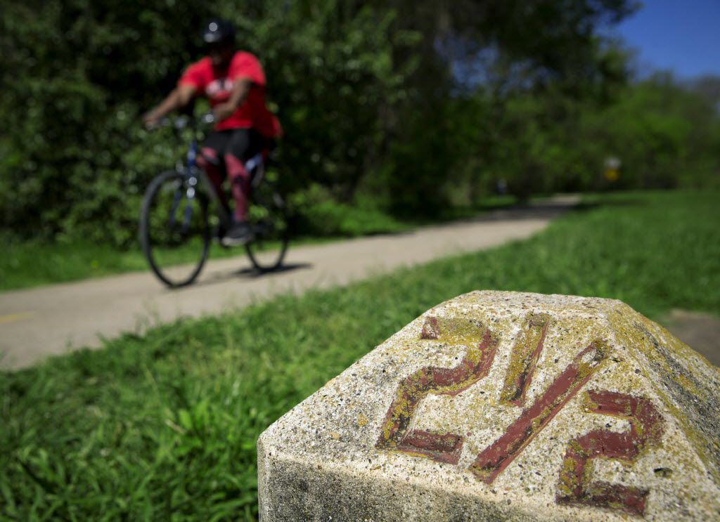 A bicyclist passes a mile marker along White Rock Creek Trail Saturday, April 2, 2016 in Dallas. (G.J. McCarthy/The Dallas Morning News)