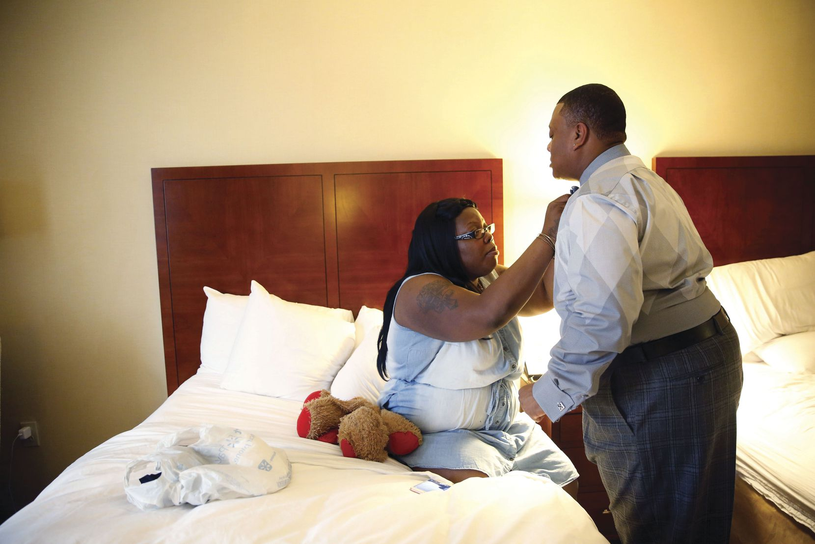 Trenton Johnson, a transgender man, lets his fiancée, Bridget Charleston, straighten his bowtie in his hotel room before the Black Trans Advocacy Conference gala in Dallas.
