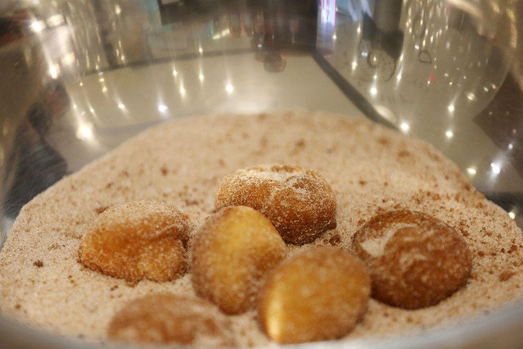 Cinnamon sugar doughnuts being dusted.