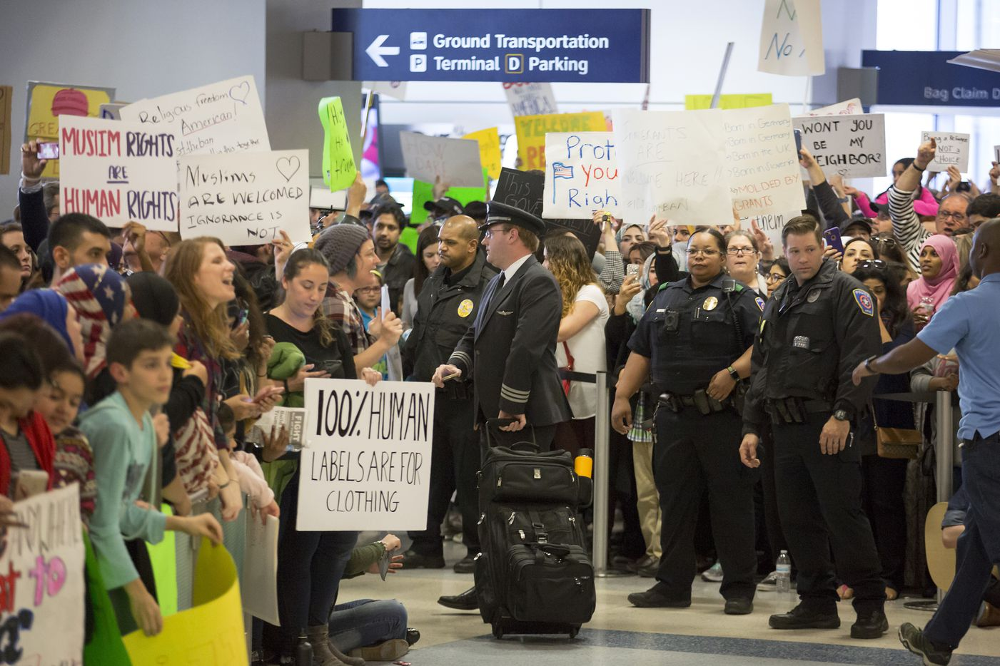 Police keep a walkway clear in the international arrivals hall at DFW International Airport as protestors fill the hall in opposition to President Donald Trump's executive order barring certain immigrants on Sunday, Jan. 29, 2017.