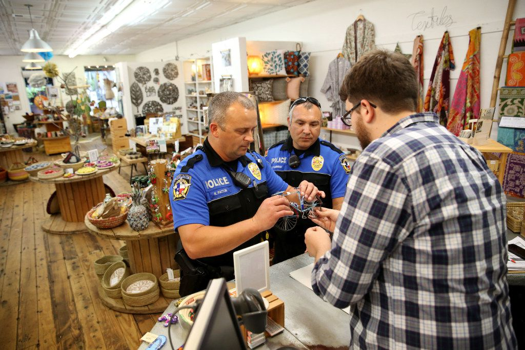 Andrew Jones (far right), owner of Fair and Square Imports, shows McKinney neighborhood police officers Randy Patton (left) and Sgt. Damian Guerrero a bicycle made out of recycled material at the store in downtown McKinney. (Rose Baca/The Dallas Morning News)