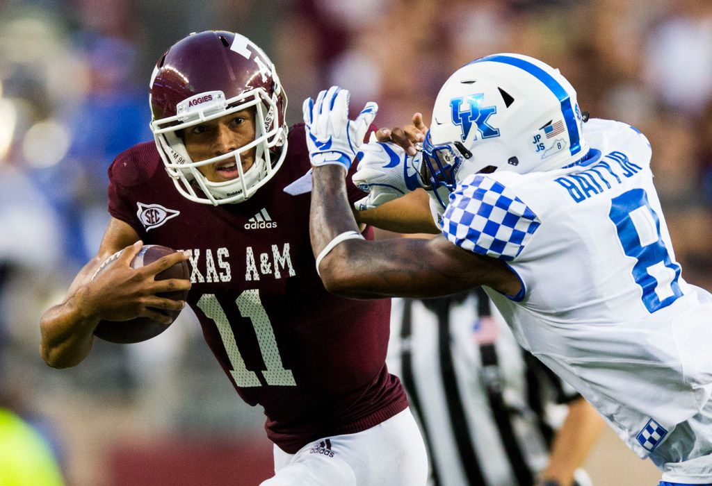 FILE - Texas A&M Aggies quarterback Kellen Mond (11) stiff arms Kentucky Wildcats cornerback Derrick Baity Jr. (8) during the second quarter of an NCAA football game between Kentucky and Texas A&M on Saturday, October 6, 2018 in College Station, Texas. (Ashley Landis/The Dallas Morning News)