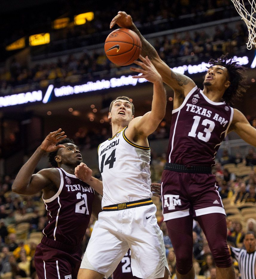 Missouri's Reed Nikko, center, battles Texas A&M's Brandon Mahan, right, and Christian Mekowulu, left, for a rebound during the first half of an NCAA college basketball game, Saturday, Feb. 9, 2019, in Columbia, Mo. (AP Photo/L.G. Patterson)