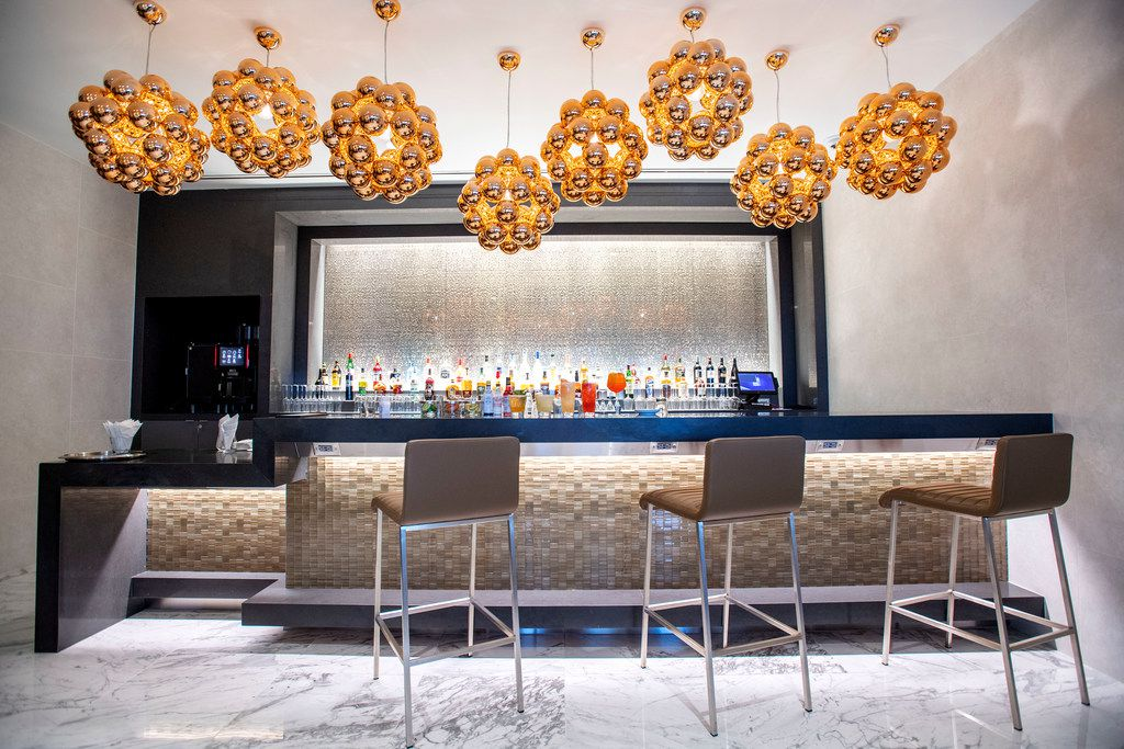Modern light fixtures hang above the bar of the Flagship First Dining area in the new American Airlines Flagship Lounge on Monday, May 13, 2019 in Terminal D at DFW Airport in Grapevine, Texas. (Jeffrey McWhorter/Special Contributor)