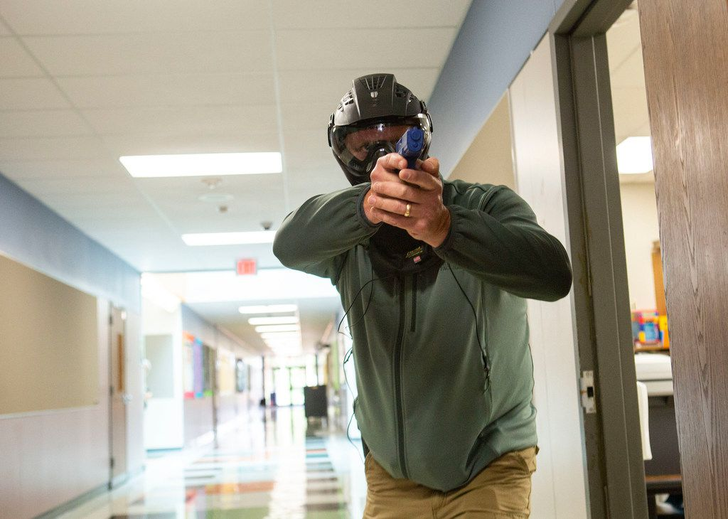 A Texas school employee training to become an armed school marshal steps into the hallway after clearing out a classroom, part of a practice drill at Windermere Elementary School in Pflugerville, Texas, on August 10, 2018.