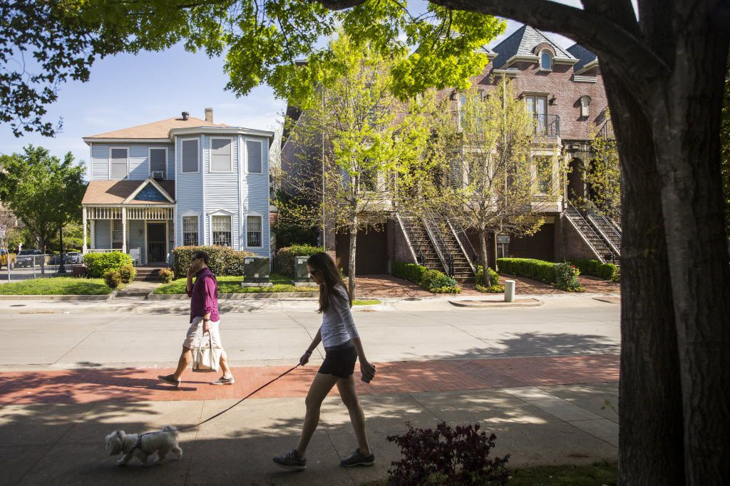 Pedestrians pass the home of Ruth Sanders in Uptown on Saturday, March 26, 2016, in Dallas. Sanders, 93, has Alzheimer's disease. She's being sued by a Dallas real estate firm over a failed deal to sell her house, one of the last historic black homes in Uptown. The home (left) is wedged between a block of new townhomes and a bar across the street. (Smiley N. Pool/The Dallas Morning News)