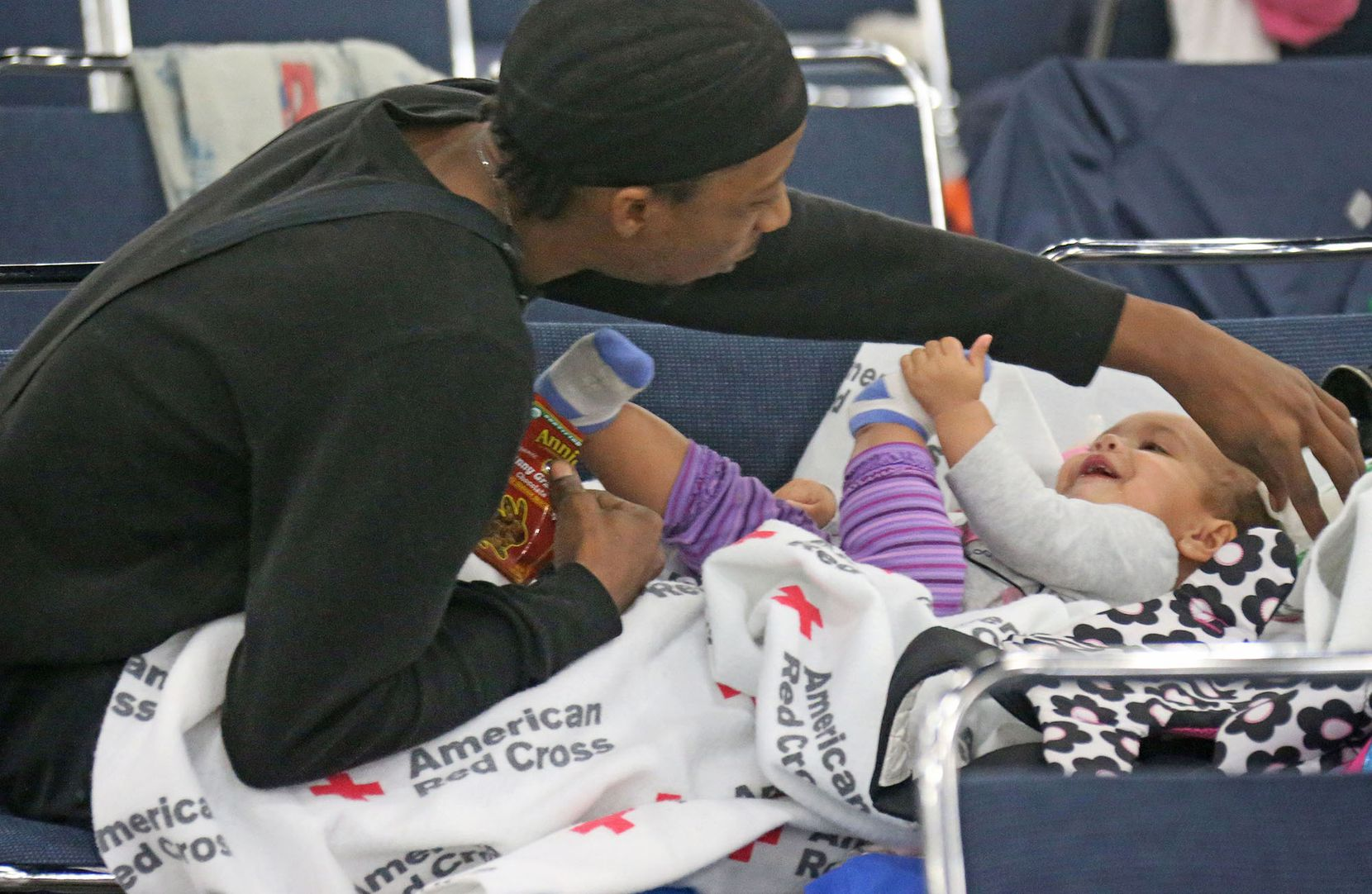 Displaced resident Darnyl Thomas plays with his daughter Riley Thomas as they try to pass the time at the George Brown Convention Center in  Houston on Monday, August 28, 2017.
