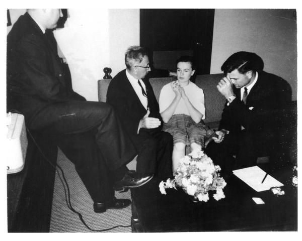 With his foot on table, Howard sits next to tape recorder, running the switch as the agents, through Russian translator Peter Gregory (second from left), question Marina Oswald. Agent Charles Kunkle holds the microphone.